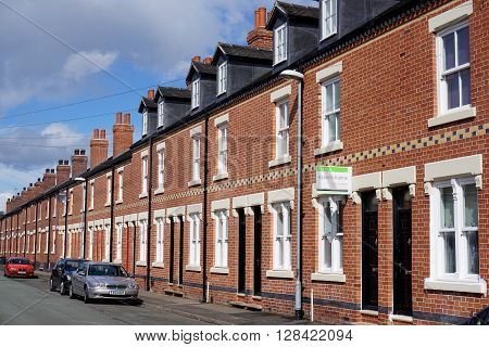 STOKE-ON-TRENT, UK - MARCH 29: A for sale sign hangs in front of a terraced house, part of a street of recently-restored residential properties in Burslem, Stoke-on-Trent, UK on March 29, 2016.