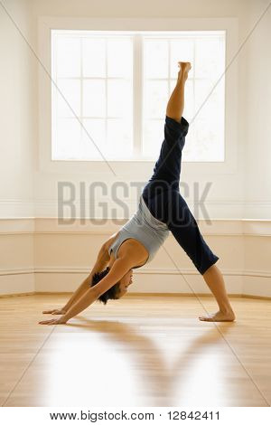Young woman doing downward dog pose with one leg raised on wooden floor indoors by sunlit window.