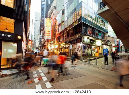 HONG KONG, CHINA - FEB 12, 2016: Motion blurs of rushing people on streets with tall glass and concrete buildings in busy district of city on February 12, 2016. There are 1223 skyscrapers in Hong Kong.