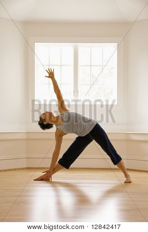 Young woman doing yoga triangle pose indoors by sunlit window.