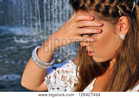 young attractive woman cooling near the fountain in hot weather
