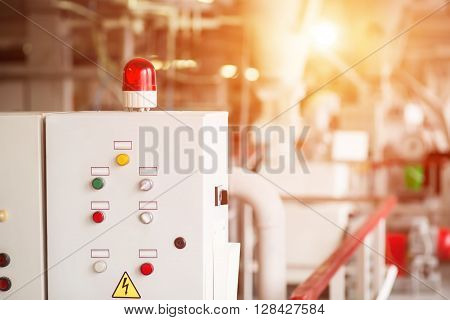 Control panel with rotating light. Buttons and switches on panel. Machine that distributes energy. Good knowledge is required.