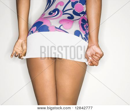 Young African-American female pulling down short dress over derriere.