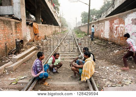 KOLKATA, INDIA - JAN 13, 2016: Group of poor men sit on the railroad tracks and have conversation on January 13, 2013. Third biggest indian city Kolkata with suburbs is home to approximately 14 mill.people