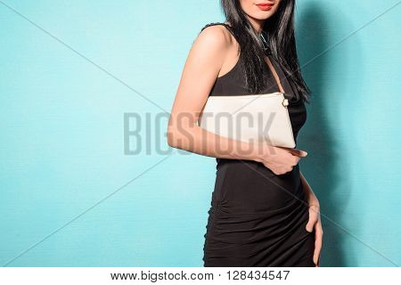 Fashionable woman with a white bag in her hands and black evening dress on blue background