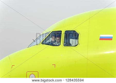 The Pilot Of The Plane S7 Airlines Waving In Greeting.