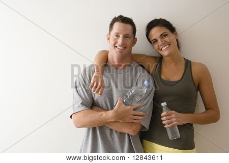 Man and woman at gym in fitness attire holding water bottles standing against wall smiling.