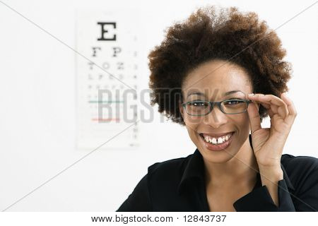 Portrait of woman with afro wearing eyeglasses with medical eyechart in background.