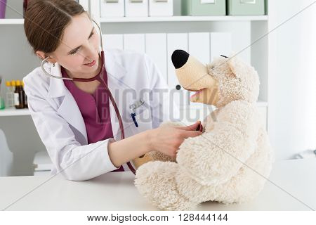 Family doctor examination. Beautiful smiling female doctor in white coat examine teddy bear with stethoscope to calm down and interest child. Playing with baby patient. Pediatrics medical concept