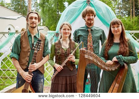 MOSCOW, RUSSIA - MAY 30, 2015: Young musicians of musical Band Polca an Ri stand against arch decorated green and white fabrics. Polca an Ri plays traditional irish music.