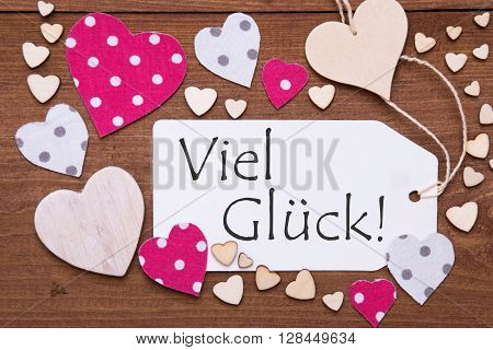Label With Pink Textile Hearts On Wooden Background. German Text Viel Glueck Means Good Luck. Retro Or Vintage Style