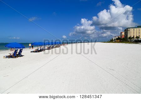 FORT MYERS BEACH, USA - MAY 12, 2015: Beach chairs and sunshades on the beach with apartment blocks and hotels on the right and the Gulf of Mexico on the left and some people walking by.
