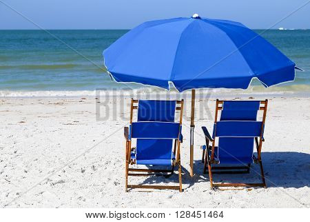 A pair of blue beach chairs and a blue sunshade on the beach in Fort Myers Beach viewing the Gulf of Mexico.