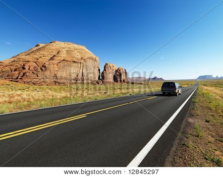Sport utility vehicle on open highway in scenic desert landscape with butte land formation.