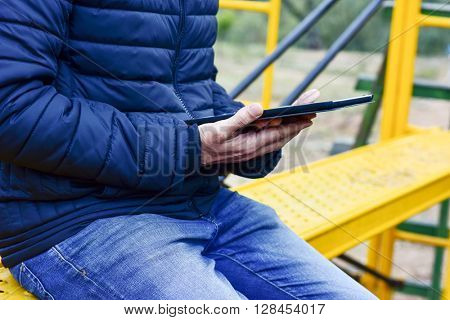 closeup of a young man using a tablet computer in a yellow scaffold, outdoors
