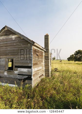 Abandoned rural wooden house in state of disrepair.