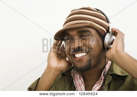 African-American mid-adult man wearing knit hat and listening to headphones smiling.