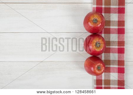 Red apples are in a row on a wooden surface with checkered kitchen tablecloth in top view. Table decoration. Healthy food. Improving health. Beating diarrhea and constipation. Boosting immune system.