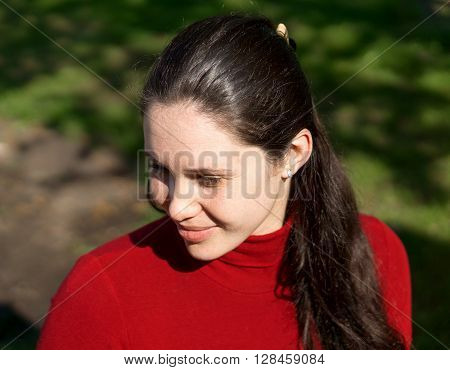 Portrait Of Young Happy Brunette Girl In Jeans And Red Jacket On Grass