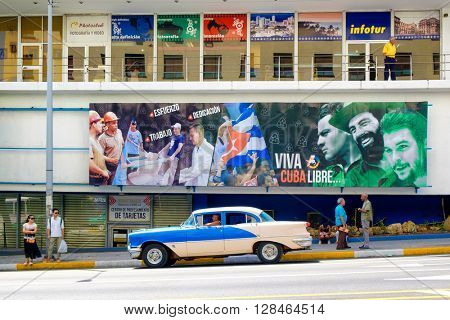 HAVANA,CUBA- APRIL 29,2016 :  An old classic car crosses in front of a billboard with revolutionary slogans in Havana