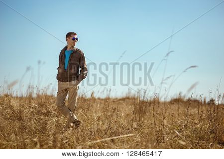 Young fashionable man with sunglasses and windbreaker standing outdoor. There is a  field as background.
