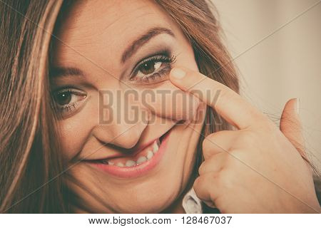 Expression and positive emotions playful gestures. Woman touch eyelid with finger smile make silly face and have fun.