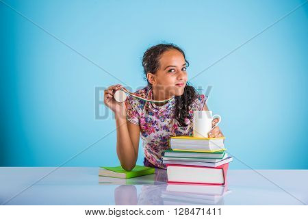 indian studious girl showing gold medal or success sign, leaning over table with pile of books, asian small girl and success concept, 1st in studies concept, indian schoolgirl and merit concept