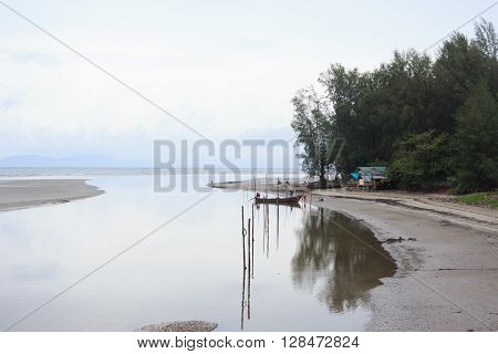 refect of fishing boat on sea after rain and mist