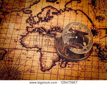 Travel geography navigation concept background - vintage retro effect filtered hipster style image of old vintage retro compass with sundial on ancient world map