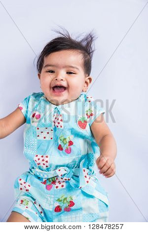 Smiling Indian infant or baby girl on the floor, top view