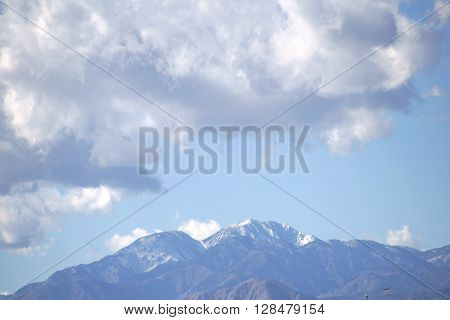 The snowcapped peak of Mount San Jacinto in the San Jacinto Mountains with clouds over the mountains.
