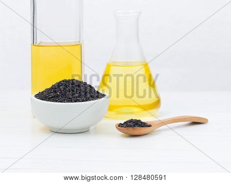 Sesame in a bowl and spoon with oil in laboratory glass setup on wooden table.