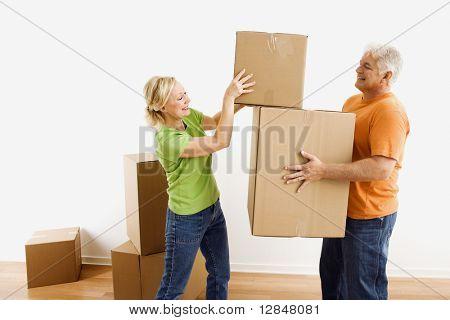 Mann mittleren Alters mit bewegenden Kartons während Frau legt einen Stapel.