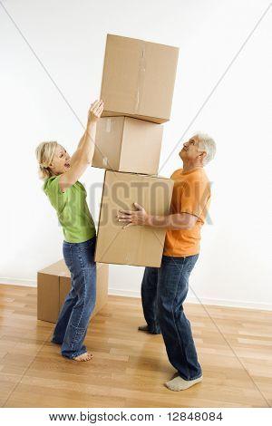 Mann mittleren Alters halten Stapel Kartons Umzugskartons während Frau stellt ein anderes an.