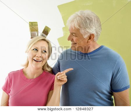 Portrait of happy adult couple standing in front of half-painted wall while man makes bunny ears with paintbrushes behind woman's head.