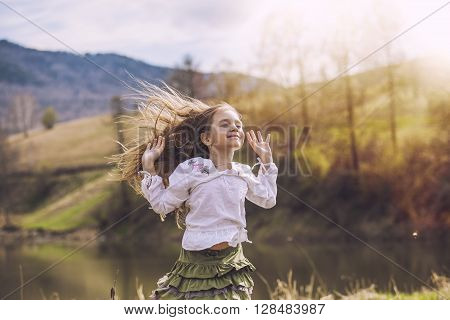 Little, Beautiful Baby Girl Laughing And Smiling On The Background Of Nature