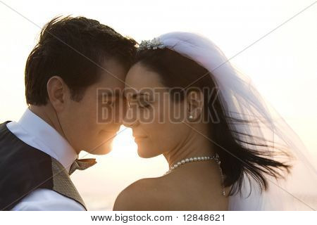 Backlit image of a newlywed couple on the beach. Horizontal shot.