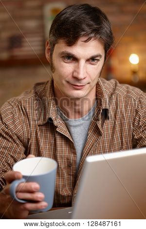 Thoughtful man using laptop computer, drinking tea.