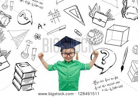 childhood, school, education, knowledge and people concept - happy boy in bachelor hat or mortarboard and eyeglasses showing strong hands with doodles