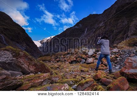 younger female photographer take a photograph in franz josef glacier important traveling destination in south island new zealand