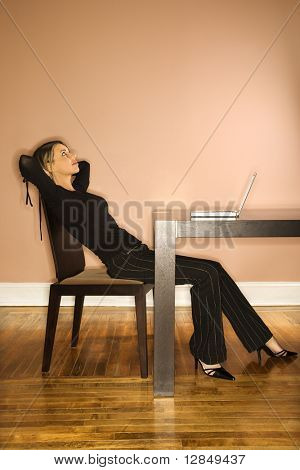 Attractive young businesswoman slouching in chair and looking up. A laptop is on the table in front of her. Vertical shot.