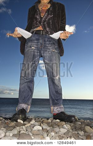 A young man poses at the beach. He is viewable from the neck down, holding a cigarette, and is showing his empty jeans pockets. Vertical shot.