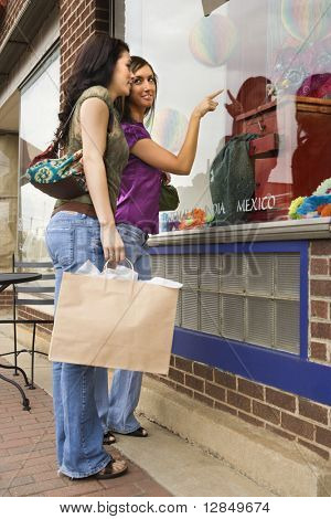Low angle view of young women pointing to items in an international interior design store window. Horizontal shot.