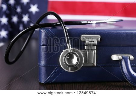 Stethoscope with blue suitcase on a table