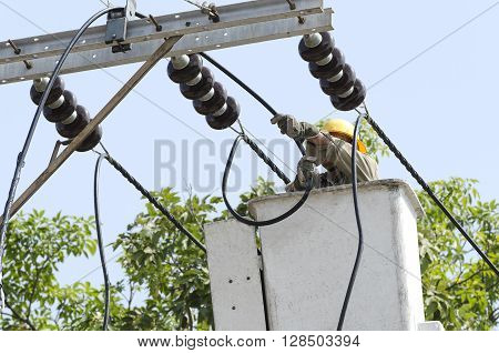Close up view of one electrician is repairing electric power system on an electtic pole from lift bucket.