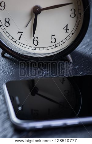 Black alarm clock with cell phone on a wooden table