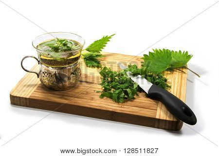 Preparing nettle tea leaves knife and teacup on a wooden cutting board isolated with shadows on a white background selected focus narrow depth of field
