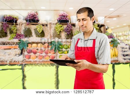 shopman in the greengrocer and fruit shop uses a tablet