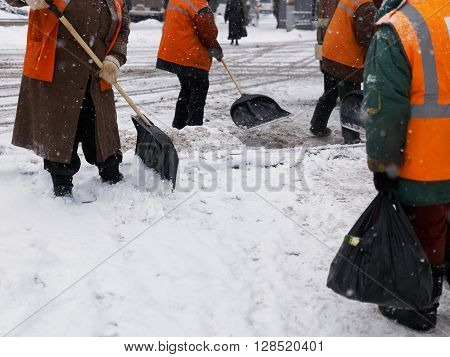 A few street janitors weared orange vests clear street from snow during snowfall