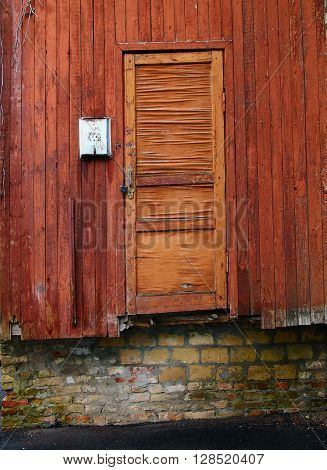 Metallic mailbox on the red wood wall next to aged cracked red wood door above the brick wall